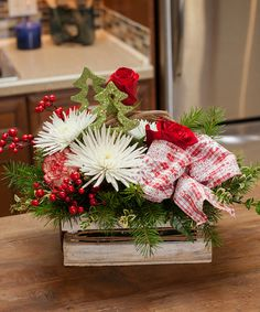 "Christmas Charm | Two green trees are nestled among fresh fir, white spider mums, red roses and peppermint carnations and red berries in a rustic basket.  10""t x 12""w"