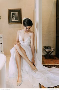 A strappy detailed white wedding dress with classic hair and closed toe shoes