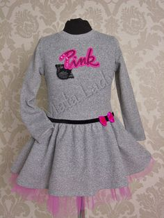 Elegancka sukienka Pink w odcieniu szarości, delikatnie rozkloszowana. Dół sukienki to połączenie materiału bawełnianego z tiulem w kolorze różowym, odszyty podszewką. Sukienka posiada długi rękaw oraz kryty zamek z tyłu kreacji. Przód sukienki ozdabia czarny pasek z różową kokardą.  Sukienka dostępna z dodatkami w kolorze czarnym lub czerwonym.