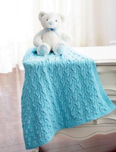 The staggered squares create a lacy detail effect for this knit baby blanket. This is a sporty and light comforter for baby.