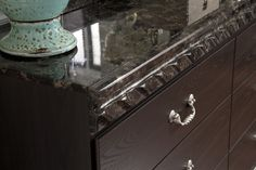The dresser has a luxurious, profiled faux-marble top