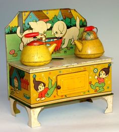 Vintage tin litho toy stove with tea kettles.