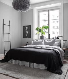 Scandinavian bedroom, dark bed cover, large window, black and white wall art, feather pendant lamp. Home Decor Bedroom, Decor Room, Dark Bedding, Home Interior, Interior Design, Scandinavian Bedroom, Scandinavian Furniture, Minimalist Bedroom, White Walls