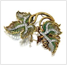 Marcus & Co. | Plique-à-jour enamel and diamond leaf brooch - circa 1900. The double-leaf motif of shaded green plique-à-jour enamel accented with small old-mine and single-cut diamonds, mounted in 18 karat gold and platinum.