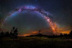 Milky Way over Devils Tower, northeastern Wyoming. Seen against the night sky's thin, pale clouds and eerie green air glow, star clusters and nebulae of the Milky Way arc toward the galaxy's central realm at right.
