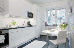 #Cocina blanca con suelo oscuro.