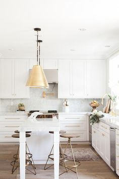 Goodman Hanging Lamps in Antique Brass hangs over a white kitchen island topped with gray and white quartzite lined with round brass and wood counter stools, Arteriors Wyndham Swivel Counter Stools.