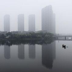 Dos hombres reman en un río donde altos edificios se reflejan durante una mañana brumosa en Shaoxing, provincia de Zhejiang, China. Foto: Reuters