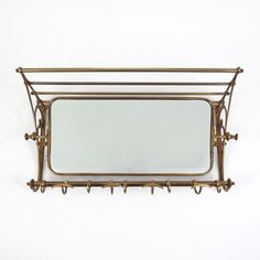 This brass coat rack features a brass frame that holds a swivel mirror.  Shipping cost to UK is £30