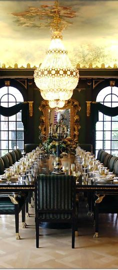 Ah, a dining room after our own hearts!  A fully embellished mirror, brassed accents on the table legs, and a table set for a banquet!
