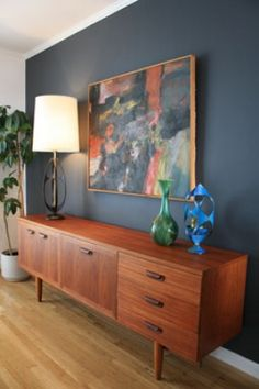 Teak credenza against dark blue/grey accent wall