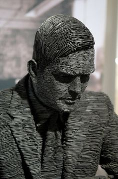 Life-size sculpture of Alan Turing made of stacked Welsh slate by artist Stephen Kettle.
