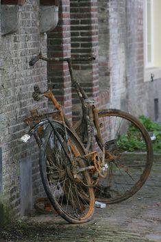 Een verroest oud fiets, geleund aan de muren van een werftkelder. Waarschiijnlijk gered uit de golven van de Oudegracht.