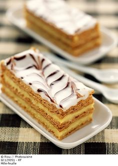 """The mille-feuille (""""thousand sheets""""), vanilla slice, custard slice, also known as the Napoleon, is a pastry of French origin. Traditionally, It's made up of three layers of puff pastry, alternating with two layers of pastry cream, but sometimes whipped cream, or jam are substituted. The top pastry layer is dusted with confectioner's sugar, and sometimes cocoa, or almonds. Alternatively the top is glazed in alternating white and chocolate stripes, and combed."""