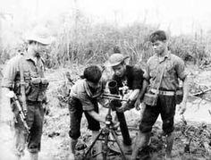 North Vietnamese Army soldiers set up an 82mm mortar. One of them wears a chest rig and carries a Type 56 assault rifle.