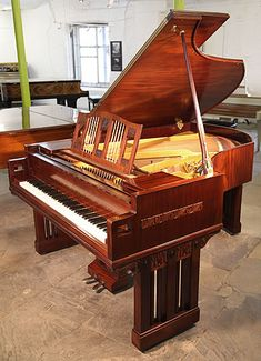 A 1916, German Arts and Crafts, Ibach grand piano with a mahogany case and carved panel detail. Rectangular lyre with 3 circular columns. Rectangular style and columns continued on legs with carved foliage detail at top. Piano cheeks feature square cut indents. Music desk features twisted brass spindles.