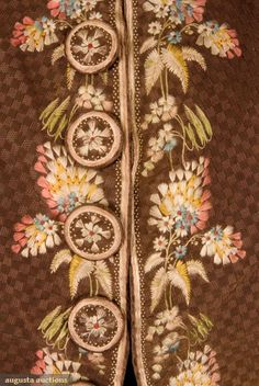 "GENT'S EMBROIDERED FORMAL COAT, 1775-1800. Brown uncut voided velvet in checked pattern, embroidered with silk multi colored brush-like flowers, standing band collar, trimmed with twenty six large embroidered buttons, shaped pocket flaps, long fitted sleeves ending in 3.25"" embroidered cuff, upper body padded with cotton batting, cream silk satin lining."