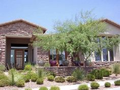 Frontyard desert landscaping design with native plants. Professional designs like this allow for spacing and future growth considerations to give an overall balance to the plan. The decorative rocks also compliment the brickwork. Picture compliments of www.horticultureunlimited.com