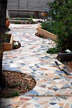 So I wanted something really unique in my backyard.  We visited a local tile store and collected all the stuff they were throwing out.  Then we busted up the tile (the kids loved this part), we poured our walkway, and then set the tile pieces in thin set.  After they were dry, we did the grout.  We also designed a cross with a deeper red tile & a crown of thorns in black at the end of the walkway in front of the fire pit.  This I LOVE!