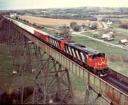 Diesel locomotives HP-616 2116 and 2115 built by Montreal Locomotive Works with a container train  Salmon River Bridge, New Brunswick, Canada  Oct/ 1983  Photographer: George Hunter  Subject: Diesel locomotives / Containerization / Montreal Locomotive Works Ltd  Image No.: CN009332  CSTMC/CN Collection
