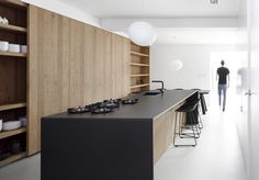 A Foscarini Gregg Pendant hangs above the kitchen table. The island is made of oak with a thin, black stone countertop.