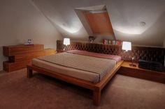 Aranżacja przestronnej sypialni na poddaszu w ciepłych barwach. Duża sypialnia na poddaszu w nowoczesnym stylu. Pomysły i inspiracje na wystrój wnętrz.