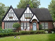 Tudor home, sharp paint job with blue door via HGTV Mag - cream colored stucco, dark trip, blue door Tudor House Exterior, Exterior House Colors, Exterior Design, Style At Home, Estilo Tudor, English Tudor Homes, Exterior Paint Schemes, Tudor Cottage, Tudor Style Homes