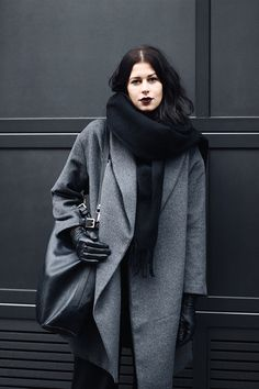 Elisa from the Fashion- and Lifestyleblog www.schwarzersamt.com is wearing a grey woolen coat from H&M with black wide leg marlene pants vom MONKI, a black one shoulder bag from MANGO, black shiny slipper and a black scarf from TOPSHOP. It's a minimal and monochrome style in black and grey.