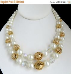 Vintage Kramer Faux Pearl Double Strand Necklace. Faux Pearls, Faceted Clear Beads and Gold Tone Filigree Ball Beads in two sized strands, with a hook clasp and extension beads. The Necklace strands are approx. 14 and 16 long The extension faux pearl beads are 3 long Signed Kramer on the Hook Clasp The necklace is in very fine condition A gift box is included  Find more Vintage Necklaces here: http://etsy.me/1Pjijeo  ➜Want to save for later? Click on the Add to button to create a…