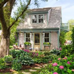 Backyard Garage Becomes Dreamy Guest Cottage Cedar shingles cured by the salt air, window brackets borrowed from the main house, a sunny balcony, and a shady elm give the former garage a storybook look.The entry lights and cast-iron front step are sa