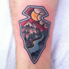 Mountains, arrowhead, and forest tattoo