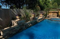 raised bond beam (retaining wall), stone tile and stack stone finish for the pool.