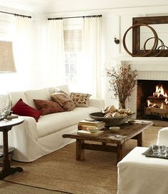 Rustic coffee table and seagrass rug bring texture and color to this white living room. Fireplace adds warmth.