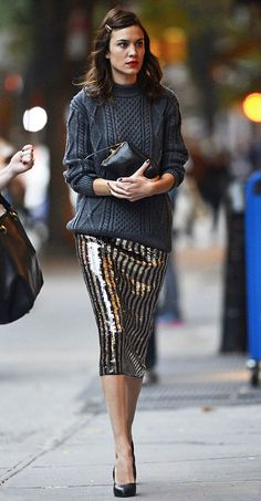 Shop this look on Lookastic:  http://lookastic.com/women/looks/charcoal-cable-sweater-black-clutch-black-and-gold-pencil-skirt-black-pumps/5465  — Charcoal Cable Sweater  — Black Leather Clutch  — Black and Gold Vertical Striped Sequin Pencil Skirt  — Black Leather Pumps