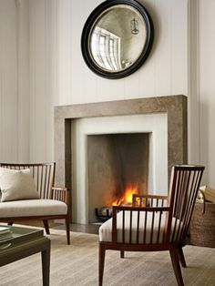 Simple fireplace, round convex black mirror, pair of mid century modern wood chairs!