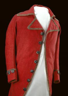Red Wool Coat of Auguste Chouteau, 1780. Single breasted, cutaway style with tails, fitted with 3 back seams. There is a large, wide rolled collar with small, pointed lapels. The coat has 27 buttons: All buttons are wood covered with metallic thread that is woven in such a way as to divide the buttons into quadrants. The buttons are gray in color, probably once gold, the metal has oxidized. Cream-colored silk lining. (c) Missouri History Museum