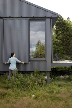 A Tiny Cabin is This Writer's Off the Grid Getaway - Photo 14 of 20 - When Alex or Bruce leave the island, closing up shop is as simple as sliding panels of corrugated metal into place to protect the windows. Metal Building Homes, Building A House, Building Ideas, Building Plans, Architecture Durable, House Architecture, Casas Containers, Sliding Panels, Sliding Doors