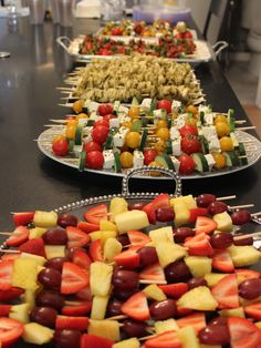 Party skewers: pesto tortellini, chicken sausage and peppers, fruit salad, caprese salad, and greek salad!