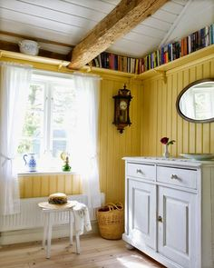 Room in a Swedish summer house, butter yellow walls, shelf of books running under ceiling - love the yellow and white, and the pretty curtains Small Space Living, Small Spaces, Ceiling Shelves, Ceiling Beams, Tall Ceilings, Yellow Walls, Bed And Breakfast, Home Interior Design, Bookshelves