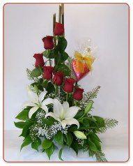Caracola con 7 rosas y lilium en base simple forrada con papel arroz y bambú de fondo. Mide aproximadamente 70-80 centímetros de alto.