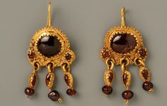Earrings with garnets:    This pair of gold earrings is perfectly preserved. With a curved barbell gold they could be confirmed in the ear. The rod is attached to a solid round plate on which a large oval shell is fixedly put in a notched setting. The garnet is flanked by two smaller bomblets. The use of ornamental stones in jewelry took in the Roman Empire expanded enormously. From distant areas such as India were precious stones imported.      Date: 0-100  material: metal, gold, garnet