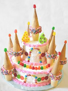 Candy Castle Cake (Easy Cake Decorating) - This cake is made simply with a two tiered cake, sugar cones, cake cones, sprinkles, gumdrops, lifesavers gummies and skittles!