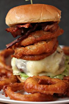Onion Ring Cheeseburger aka The Ringer- This burger is cooked on a plank, then topped with mozzarella cheese, provolone cheese, onion rings and bacon. My hubby has dubbed it The Ringer.
