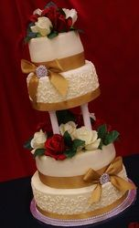 Ivory cake with cornelli lace, pillars, red and white roses, gold ribbon and brooches