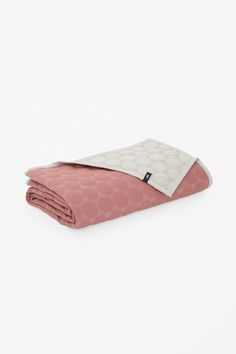 This colourful quilt is made from soft cotton with a tactile polygon design and contrasting underside. Lightly padded, it is finished with colour-block edges.