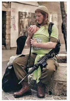רק בישראל ...Only in Israel.......A loving dad and brave soldier--in Israel. let's see, baby, guitar, rifle, yep. a typical day in Israel. even off duty, IDF members must have their rifle on their person.....