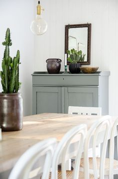 Modern farmhouse dining room with vintage blue grey cupboard, modern pendant light, pine top farmhouse table, white Bentwood chairs, and cactus on table.