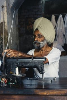 Amritsar, India - June 30, 2008: Old man  working in his small tailor shop by Alex & Berg