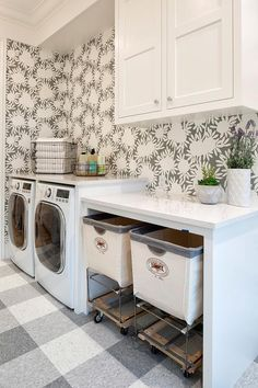 Vintage laundry bins sit beneath a white quartz countertop on a white and gray plaid tiled floor and beside an enclosed white front loading washer and dryer.