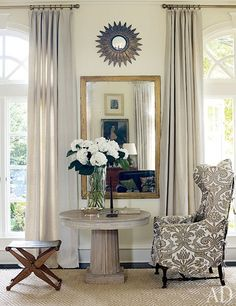 Victoria Hagan's Connecticut Home : Architectural Digest. A damask-slipcovered 19th-century English wing chair is paired with a rug by Beauvais Carpets in the living room.